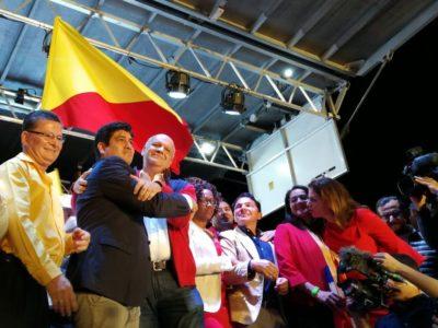 Carlos Alvarado y Rodolfo Piza se abrazan rodeados de figuras políticas del PAC y de otros partidos en la tarima ubicada en la plaza Roosevelt, en Montes de Oca